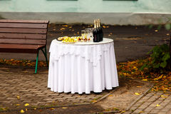 The bottle of champagne and snacks are on white round table in t Stock Photos