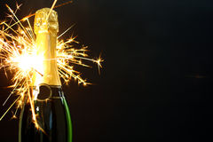 Bottle of champagne. A bottle of champagne and sparklers isolated on gray background Royalty Free Stock Photos