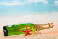 Bottle of champagne and starfishes Royalty Free Stock Image