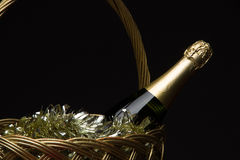 A bottle of champagne in a straw basket with New Year`s tinsel a Stock Photos