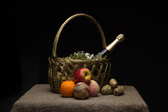 A bottle of champagne in a straw basket with New Year`s tinsel a Stock Photo