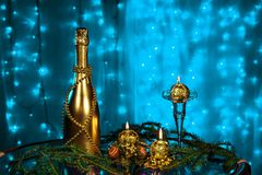 A bottle of champagne and candles in New year and Christmas on blue background Royalty Free Stock Photos