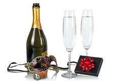 Bottle of champagne with two flutes. And party mask Royalty Free Stock Photography