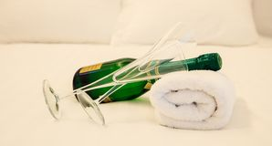 Champagne`s bottle and couple of glasses laying on white towel. White bedding backdrop, closeup view Stock Images