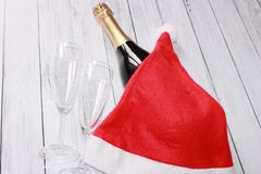 A bottle of champagne, two glasses and Santa Claus cap thrown on top royalty free stock photos