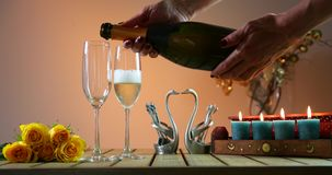 Bottle of champagne with two glasses. Woman pours champagne into glasses. Romantic evening. Womans hand put the fork into cheese . yellow cheese with fresh stock video footage