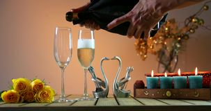 Bottle of champagne with two glasses. Woman pours champagne into glasses. Romantic evening. Yellow Roses, blue candles, wooden table, heart in the middle stock video footage