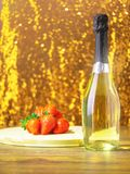 Bottle of champagne on a wooden table, strawberries on a wooden block, Gold glittering background. Bottle of champagne on a wooden table, strawberries on a stock photography