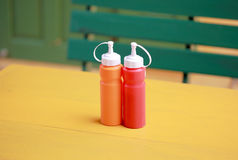 Bottle of chili and tomato sauce on yellow table Stock Photography