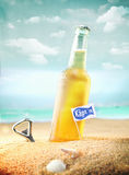 Bottle of chilled beer. Beautiful photo of a chilled beer and a bottle opener on the beach tagged as Kapt'n stock image