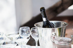 Bottle of chilled champagne, wineglasses are in ice bucket for g. Uests on wedding reception before wedding ceremony stock images
