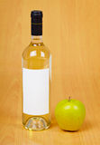 Bottle of cider and apple on table Stock Images
