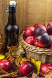 Bottle of cider and apples in the basket. On wooden background Royalty Free Stock Photo