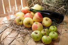 Bottle of cider with some apples and straw Royalty Free Stock Images