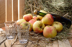 Bottle of cider with some apples and straw Royalty Free Stock Image