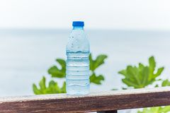 Bottle with clean drinking water against the sea royalty free stock images