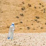 Bottle of clean drinking water in a dry desert, copy space.  stock photo