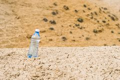 Bottle of clean drinking water in a dry desert. Copy space royalty free stock images