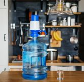 Bottle of clean water 19 liters with blue pomp in the interior of the apartment on the background of the kitchen. Clean and health. Y water Royalty Free Stock Photos
