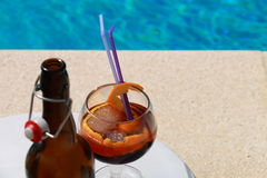 Bottle and cocktail on the edge of the pool. Open bottle and cocktail decorated with orange peel and straws on the edge of a pool Stock Images
