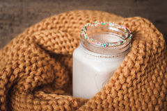 A bottle of cocoa with a yellow knitted scarf Stock Photo