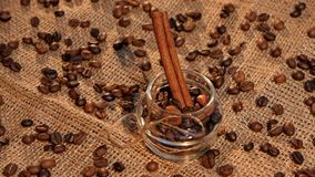 Bottle with coffee beans and cinnamon on sacking. Bottle with roasted coffee beans and cinnamon on sacking with coffee beans stock video