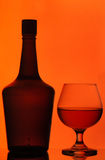 Bottle and cognac glass Stock Photos