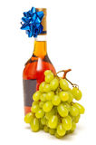 Bottle of cognac and grapes Royalty Free Stock Photos