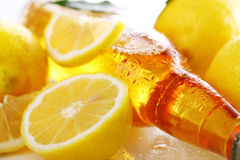 Bottle of cold beer with fresh lemons Royalty Free Stock Images