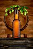 Bottle of cold beer and old barrel Stock Image