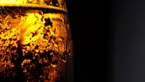 A bottle of cold beer with water splash in slow motion on a black background. Close-up stock video footage
