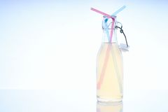 Bottle with cold drink on glass table with two straws Stock Photography