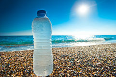 Bottle of cold fresh water on the pebble beach Royalty Free Stock Photo