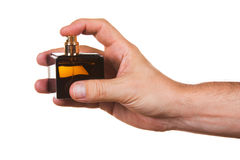 Bottle of cologne in his hand Stock Images