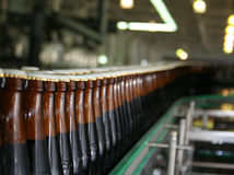 Bottle conveyor. A lot of beer bottlesmoving by conveyor Royalty Free Stock Photo
