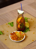 A bottle of a cool cocktail with green mint and a plate with raisins and dried apricots on a blurred light background. Royalty Free Stock Photography