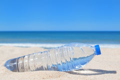 A bottle of cool water on the beach near the sea. Royalty Free Stock Images