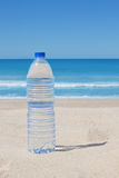 A bottle of cool water on the beach near the sea. Stock Photography