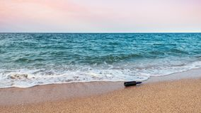 Message in a bottle on sea shore royalty free stock image