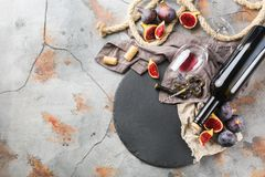 Bottle, corkscrew, glass of red wine, figs on a table Stock Image