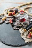 Bottle, corkscrew, glass of red wine, figs on a table Royalty Free Stock Images