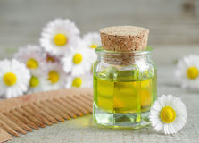 Bottle of cosmetic chamomile oil and wooden hair comb Royalty Free Stock Photography