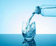Bottle with creative splashing water in the glass on blue backgr Stock Photography