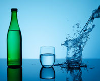 Bottle with creative splashing water in the glass Royalty Free Stock Image