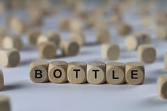Bottle - cube with letters, sign with wooden cubes Royalty Free Stock Photo