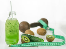 Bottle with cucumber smoothies, scattered kiwi and measuring tape on wooden table. Royalty Free Stock Images
