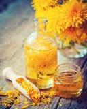 Bottle of dandelion tincture or oil, flower bunch and honey jar stock image