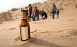 Bottle in desert. In front of thirsty young exercise group Royalty Free Stock Photography