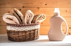 Bottle of detergent and towels in basket. stock photo