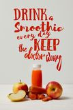 Bottle of detox smoothie with apples and carrots on white wooden surface, drink smoothie everyday keep doctor. Away inscription royalty free illustration